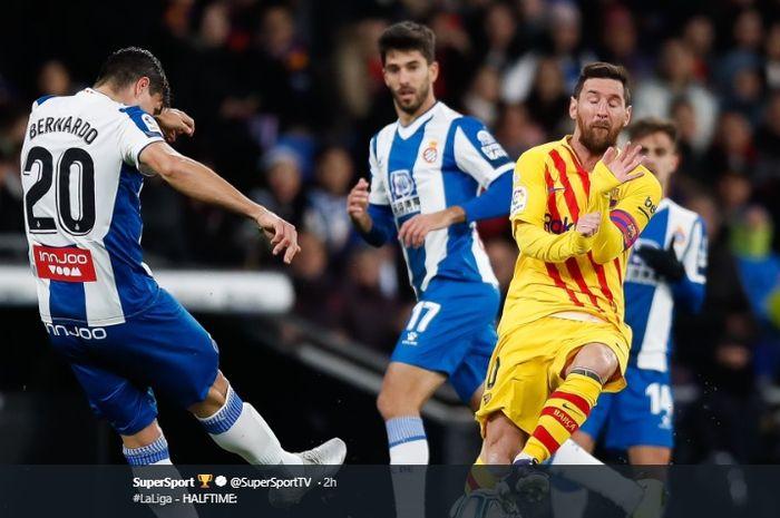 Ekspresi Lionel Messi ketika hendak memblok tendangan pemain Espanyol, Bernardo Espinosa dalam pertandingan derbi Catalunya, Sabtu (4/1/2020).