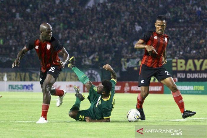 Dua pemain Persis Solo saat menghentikan pergerakan pemain Persebaya, Patrich Wanggai (tengah) saat laga uji coba bertajuk 'Forever Game' di Stadion Gelora Bung Tomo Surabaya, Sabtu (11/01/2020) malam.