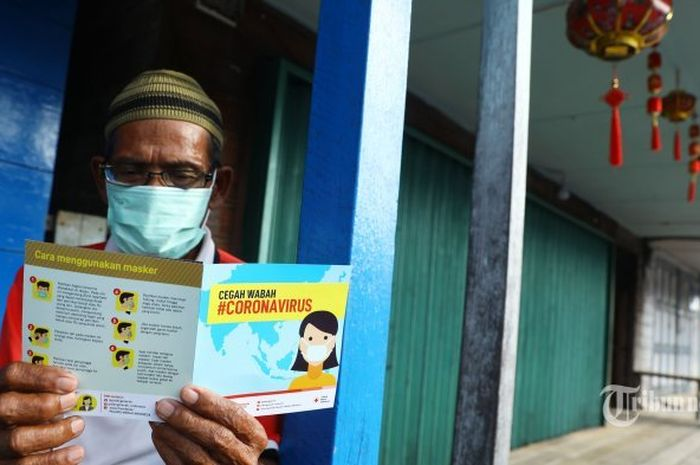 Warga membaca brosur mengenai virus corona saat sosialisasi dari PMI di Kota Tua Penagi, Natuna