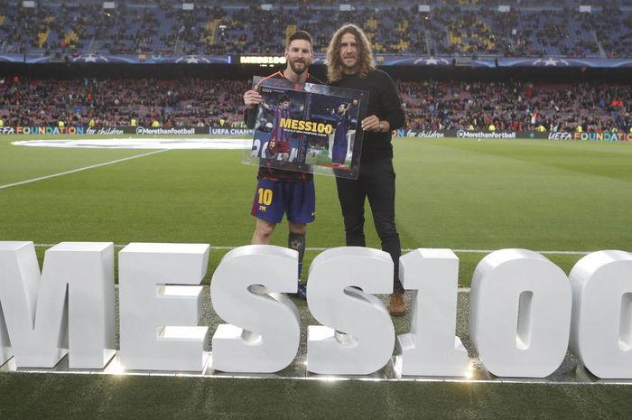Kapten Barcelona, Lionel Messi, bersama mantan rekan sekaligus legenda El Barca, Carles Puyol, saat peringatan 100 gol Messi di ajang Liga Champions.