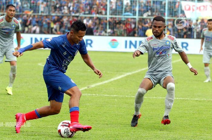 Pemain Arema FC, Dendi Santoso, dibayangi oleh pemain Persib Bandung, Ardi Idrus, dalam laga pekan kedua Shopee Liga 1 2020, Minggu (8/3/2020).