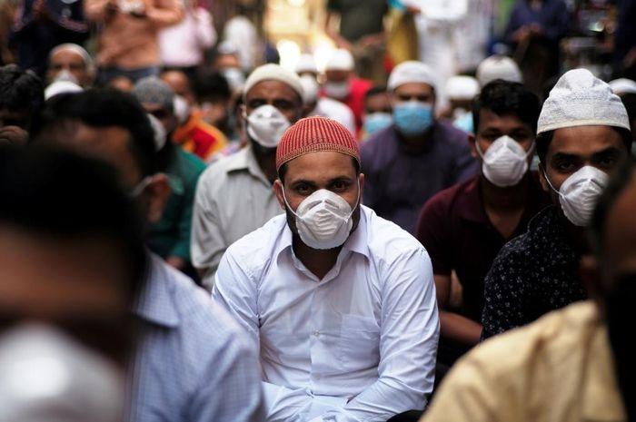 Umat Muslim mengenakan masker setelah wabah koronavirus, saat mereka sholat di jalan Manama, Bahrain, 28 Februari 2020.