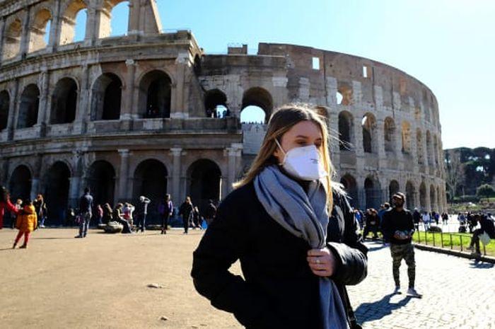 Turis mengenakan masker di luar Coliseum di Roma pada 28 Februari 2020.