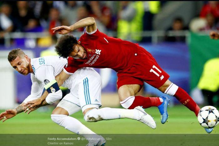 Striker Liverpool, Mohamed Salah (kanan), kehilangan keseimbangan saat dijaga ketat oleh bek Real Madrid, Sergio Ramos, dalam laga final Liga Champions di Stadion NSC Olimpiyskiy, Kiev, Ukraina pada 26 Mei 2018.