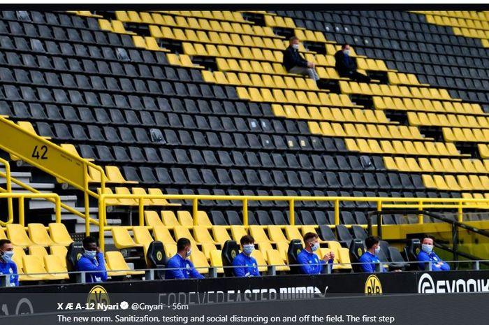 Para pemain cadangan Borussia Dortmund duduk dengan jarak renggang satu sama lain.