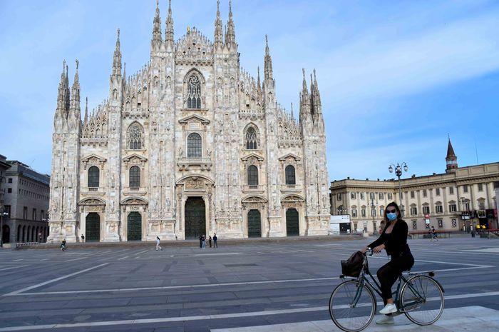 Setelah Italia mengakhiri karantina, warga berangsur kembali beraktivitas di ruang publik. Tampak pesepeda mengenakan masker sedang melintas di  Piazza del Duomo, Milan, pada pertengahan Mei 2020.