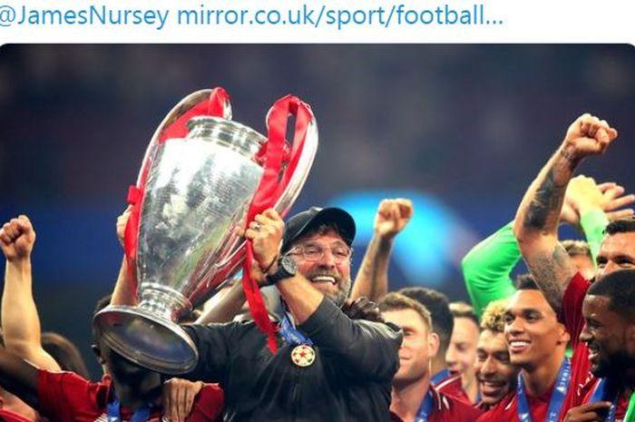 Pelatih Liverpool, Juergen Klopp, mengangkat trofi Liga Champions.