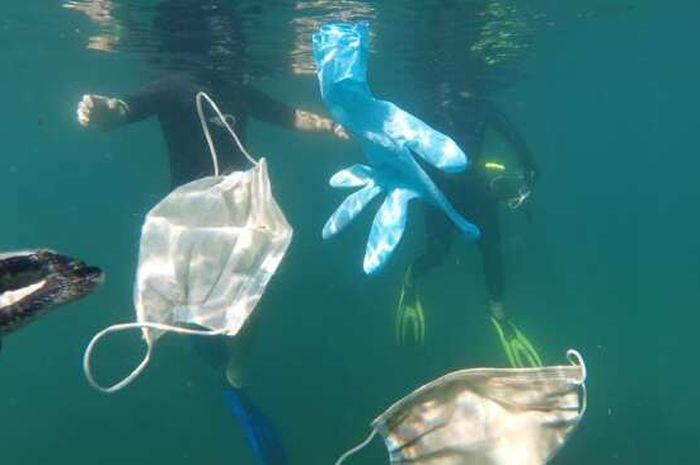 Sampah masker dan sarung tangan di lautan.