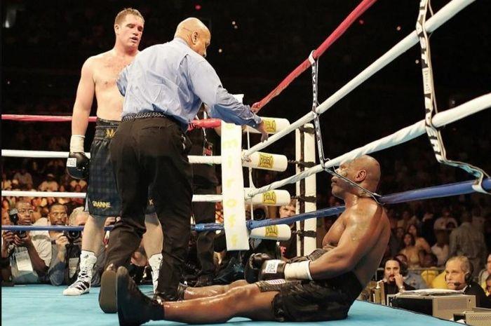 Kondisi pertarungan tinju bersejarah anrara Kevin McBride (berdiri di dekat wasit) vs Mike Tyson (duduk).