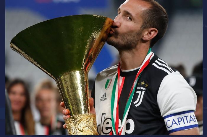 Giorgio Chiellini mencium trofi juara Liga Italia milik Juventus.