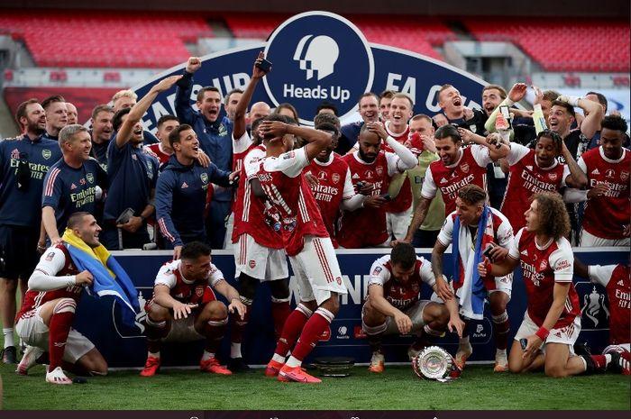 Striker Arsenal, Pierre-Emerick Aubameyang, menjatuhkan trofi saat selebrasi juara Piala FA.