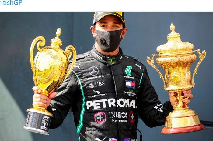 Pembalap Mercedes, Lewis Hamilton, merayakan kemenangannya pada balapan F1 GP Inggris di Sirkuit Silverstone, Inggris, 2 Agustus 2020.
