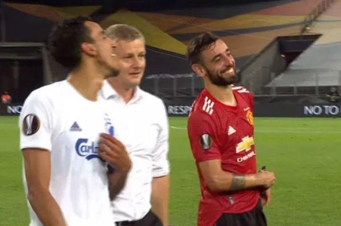 Pelatih Manchester United, Ole Gunnar Solskjaer (tengah) ngobrol dengan Bruno Fernandes (kanan) dan kapten FC Copenhagen, Zeca, seusai pertandingan perempat final Liga Europa, Selasa (11/8/2020).
