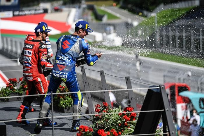 Pembalap Suzuki Ecstar, Joan Mir, merayakan hsail podium MotoGP Austria di Sirkuit Red Bull Ring, Austria, Minggu (16/8/2020). Tampak juga pembalap Ducati, Andrea Dovizioso (merah), yang keluar sebagai pemenang.