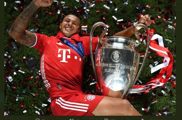 Gelandang Bayern Muenchen, Thiago Alcantara, berpose dengan trofi juara Liga Champions.
