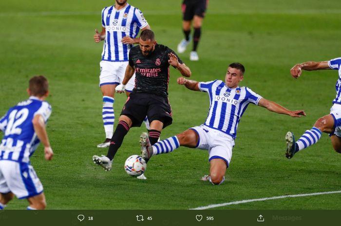 Karim Benzema melepaskan tembakan di tengah penjagaan ketat lawan dalam duel Liga Spanyol Real Sociedad vs Real Madrid, 20 September 2020.