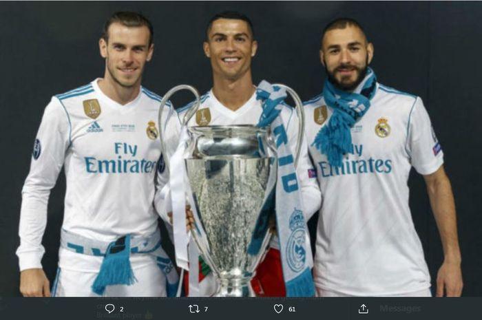 Cristiano Ronaldo diapit Karim Benzema dan Gareth Bale saat berpose dengan trofi juara Liga Champions.