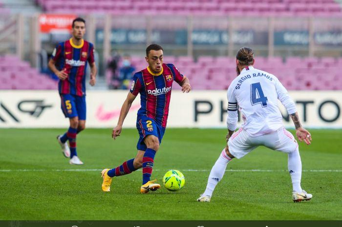 Aksi bek kanan anyar Barcelona, Sergino Dest, mencoba melewati bek Real Madrid, Sergio Ramos pada laga bertajuk el clasico.