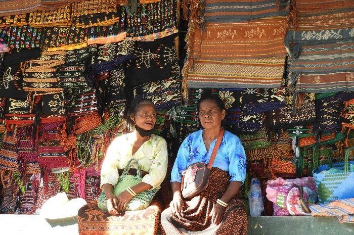 Mama-mama penenun duduk seraya menjaga kain tenun ikat jualannya di Pasar Alok, Maumere, Kabupaten Sikka. Saban Selasa, lapak tenun di pasar ini akan selalu penuh sesak dengan mama penenun menjual hasil tenunannya. Ini menjadi daya tarik wisata di Maumere.
