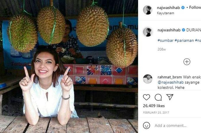 Najwa Shihab berfoto bersama durian sambil tersenyum lebar.