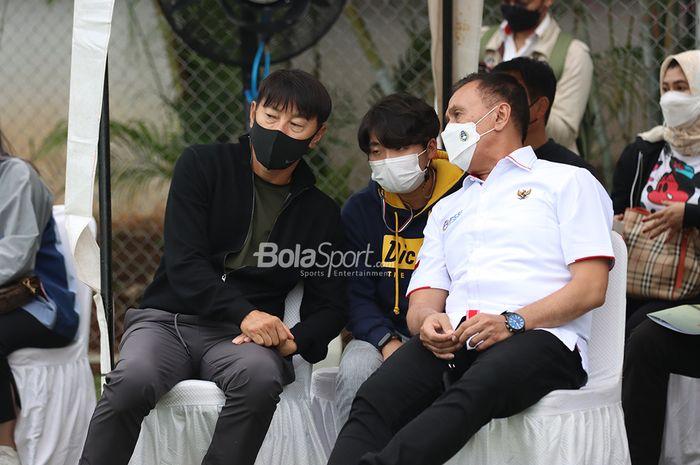 Pelatih timnas Indonesia, Shin Tae-yong (kiri) dan Ketua Umum PSSI, Mochamad Iriawan (kanan), sedang memantau latihan timnas putri Indonesia di Lapangan D, Senayan, Jakarta, 8 Maret 2021.