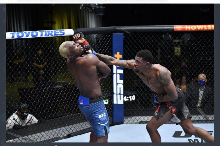 Kevin Holland (kiri) terlihat memukul Derek Brunson (kanan) selama bertanding pada ajang UFC Vegas 22, Minggu (21/3/2021).