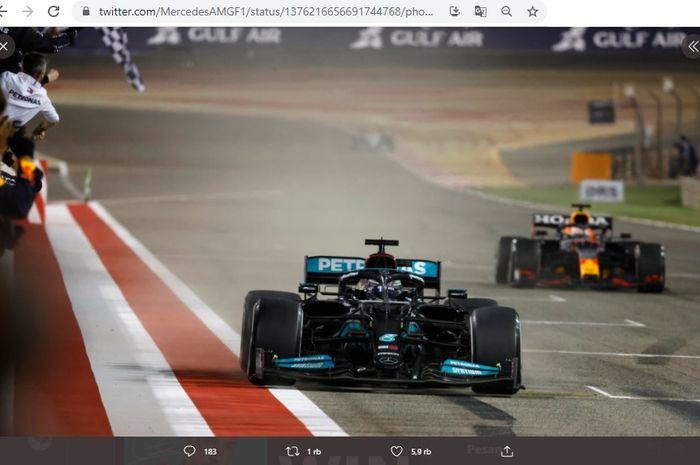 Pembalap Mercedes, Lewis Hamilton, saat memasuki garis terakhir pertama. Dibelakangnya ada Max Verstappen. Balapan terjadi pada Minggu (28/3/2021) pada seri F1 GP Bahrain 2021.