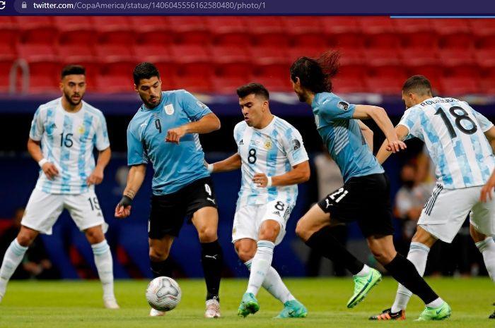 Luis Suarez tak bisa menembak ke gawang timnas Argentina yang sukses menekuk timnas Uruguay dengan bantuan dari Lionel Messi.