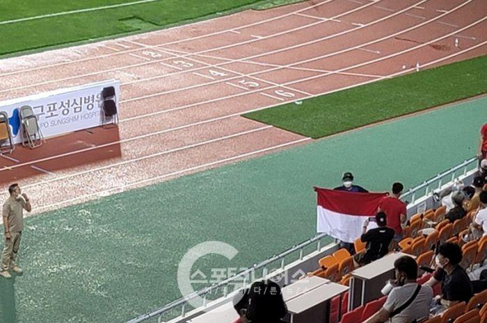 Salah seorang WNI tertangkap kamera tengah mengibarkan bendera Merah Putih di laga Ansan Greeners vs Busan IPark, Sabtu (17/7/2021).