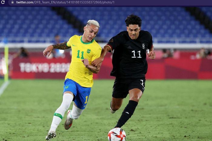 Duel pemain timnas Brasil, Richarlison (kiri), dan pemain timnas Jerman, Nadiem Amiri, dalam laga grup D Olimpiade Tokyo 2020 di Stadion Yokohama pada Kamis (22/7/2021) mulai pukul 18.30 WIB.