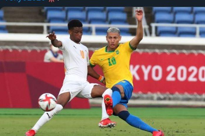 Richarlison (kanan) berebut bola dengan Amad Diallo dalam partai Brasil vs Pantai Gading di Olimpiade 2020.