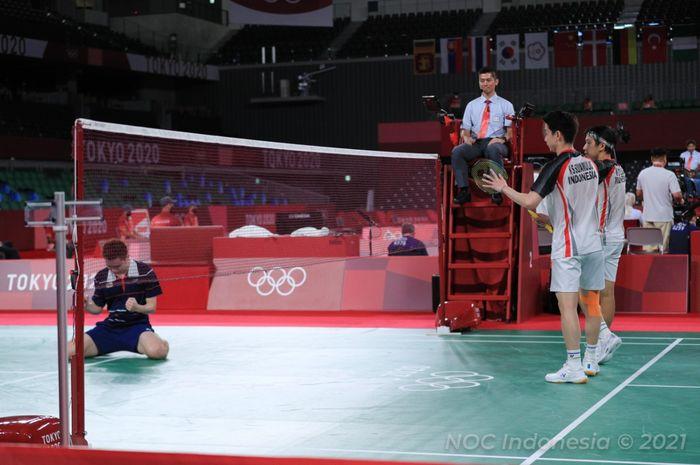 Pasangan ganda putra Indonesia, Marcus Fernaldi Gideon/Kevin Sanjaya Sukamuljo, memberi gestur selamat dengan raket mereka kepada Aaron Chia/Soh Wooi Yik (Malaysia) usai pertandingan perempat final Olimpiade Tokyo 2020 di Musashino Forest Sport Plaza, Tokyo, Jepang, Kamis (29/7/2021).