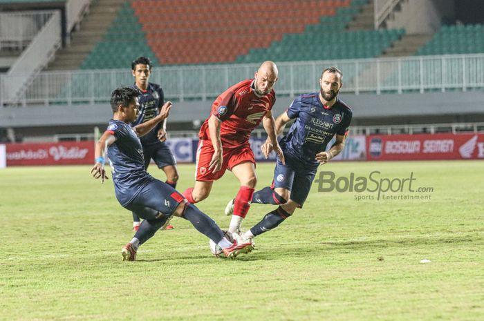Bek Arema FC, Bagas Adi Nugroho (kiri) dan Sergio Silva (kanan), sedang menjaga ketat striker PSM Makassar, Anco Jansen (tengah) dalam laga pekan pertama Liga 1 2021 di Stadion Pakansari, Bogor, Jawa Barat, 5 September 2021.