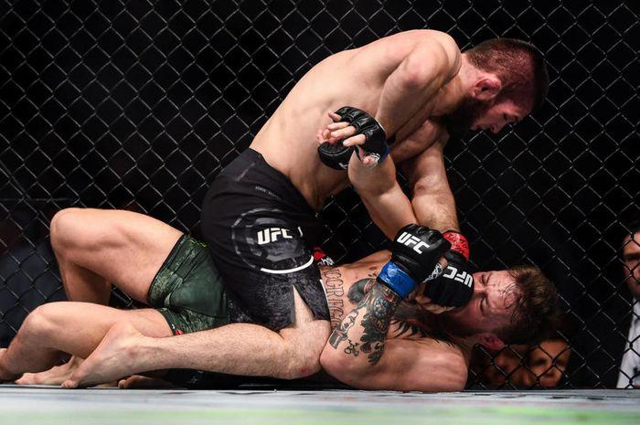 Khabib Nurmagomedov (atas) kala menghabisi Conor McGregor (bawah) pada UFC 229 beberapa tahun silam (7/10/2018).