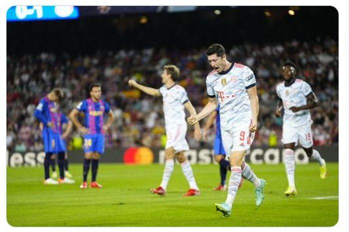 Striker Bayern Muenchen, Robert Lewandowski, merayakan gol yang dicetaknya dalam laga matchday 1 Grup E Liga Champions 2021-2022, sementara di belakangnya terlihat peman Barcelona tertunduk lesu.