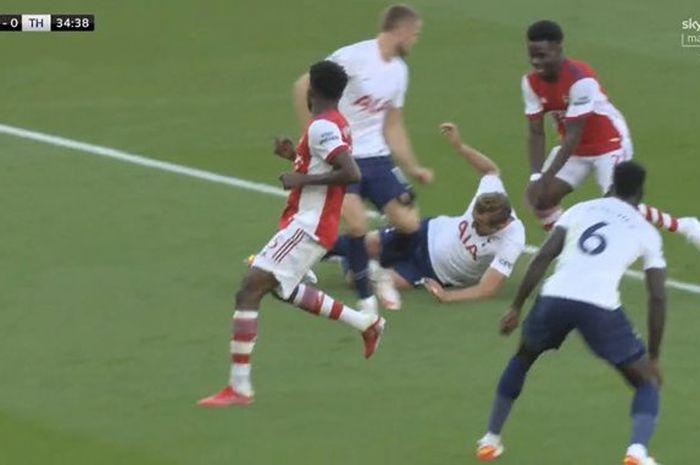 Aksi bocah Arsenal, Bukayo Saka, membuat Harry Kane sampai menggelosor demi menahan gol, tapi tetap saja Tottenham Hotspur keok pada babak pertama.