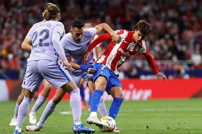 Joao Felix beradu dengan Sergio Busquets pada laga Atletico Madrid kontra Barcelona, Sabtu (2/10/2021) atau Minggu dini hari WIB.
