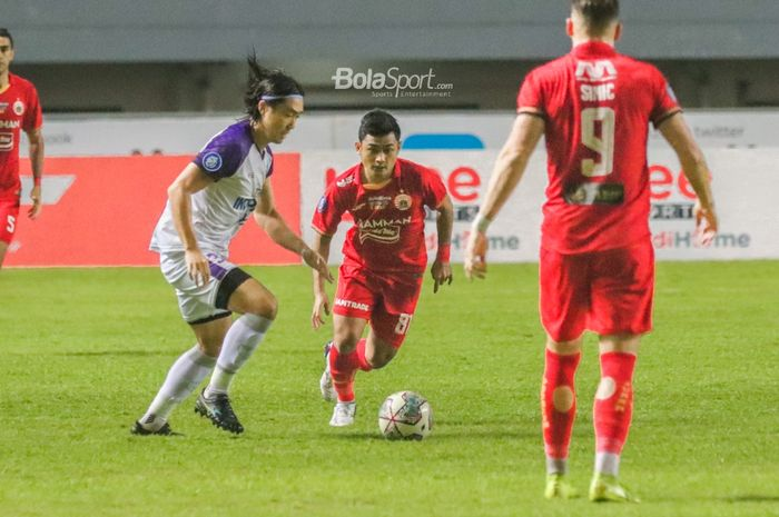 Gelandang Persita Tangerang, Bae Sin-yeong (kiri), sedang menguasai bola dan dibayangi pemain Persija Jakarta, Adrianus Dwiki Arya (tengah), dalam laga pekan kelima Liga 1 2021 di Stadion Pakansari, Bogor, Jawa Barat, 28 September 2021.