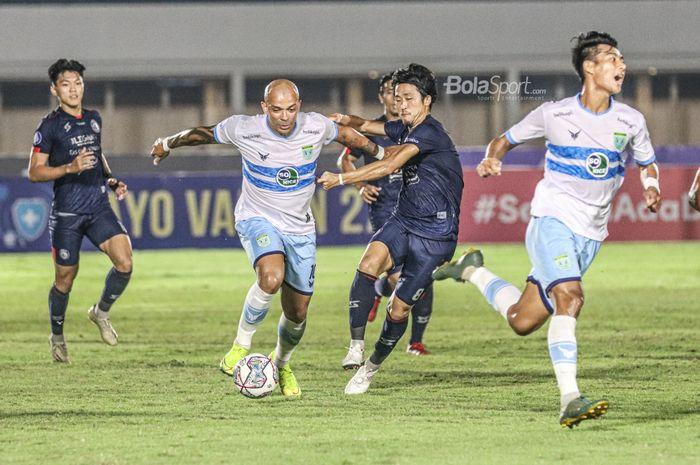Striker Persela Lamongan, Ivan Carlos (kiri), sedang menguasai bola dan dibayangi gelandang Arema FC, Renshi Yamaguchi (kanan), dalam laga pekan keenam Liga 1 2021 di Stadion Madya, Senayan, Jakarta, 3 Oktober 2021.