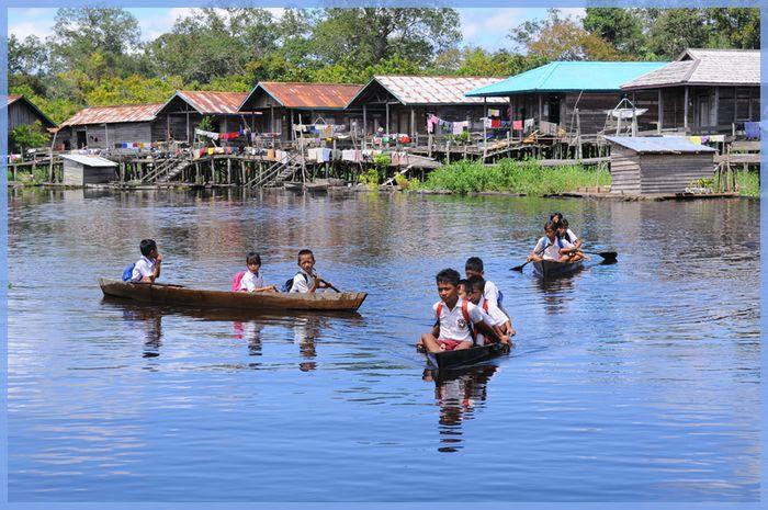 Dengan berperahu, anak-anak air di Dusun Kenasau berangkat ke sekolah. Foto: Ricky Martin | Bobo.ID
