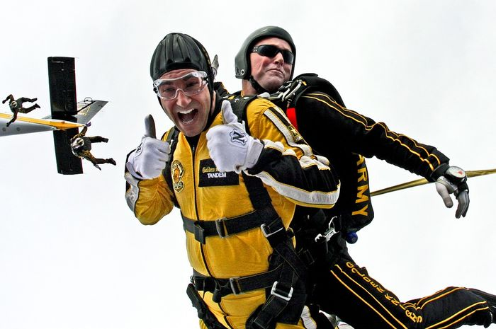 Atlet terjun payung lepas landas dari sebuah pesawat kecil.