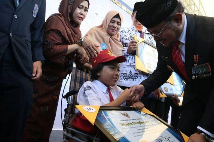 Suci Rahmawati saat menerima penghargaan juara mendongeng dari Gubernul Sulsel, Syahrul Yasin Limpo.
