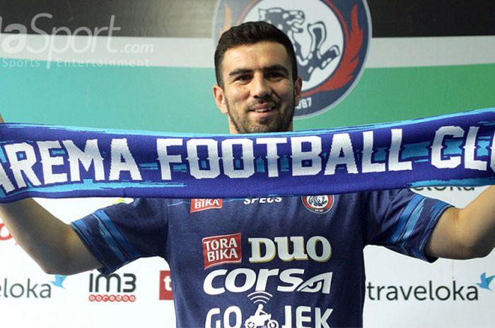 Pemain baru Arema FC asal Turkmenistan, Ahmet Atayev, mengangkat syal Arema saat diperkenalkan ke publik dalam konfrensi pers di Kantor Arema Malang, Jawa Timur, Selasa (08/08/2017) siang.