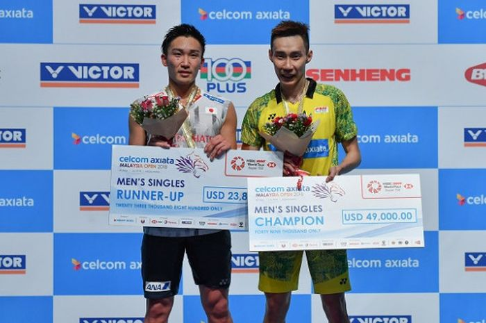 Pebulu tangkis tunggal putra Jepang, Kento Momota (kiri) dan Lee Chong Wei (Malaysia) berpose di podium masing-masing sebagai runner-up dan juara pada Malaysia Open yang berlangsung di Axiata Arena, Kuala Lumpur, Minggu (1/7/2018).