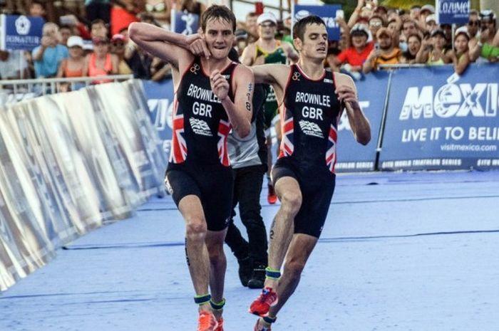 Atlet triatlon Inggris Raya, Alistair Brownlee (kiri), membantu sang adik, Jonathan Brownlee, untuk