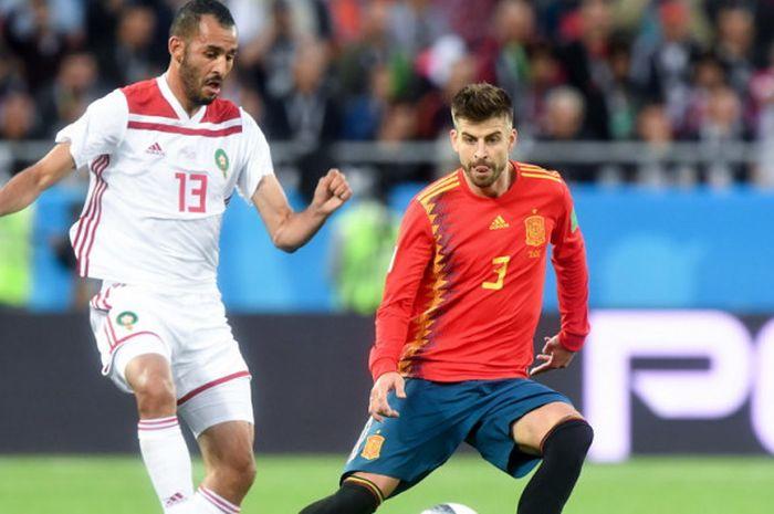 Bek timnas Spanyol, Gerard Pique (kanan), saat mengawal pergerakan pemain Maroko, Khalid Boutaib, dalam laga Grup B Piala Dunia 2018 di Stadion Kaliningrad, Kaliningrad, Rusia, pada Senin (25/6/2018).