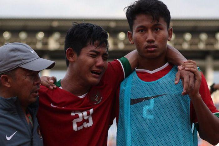 Bek timnas U-19 Indonesia, Firza Andika, meneteskan air mata seusai kekalahan di semifinal Piala AFF U-18 kontra Thailand di Stadion Thuwunna, Yangon, Myanmar, Jumat (15/9/2017).