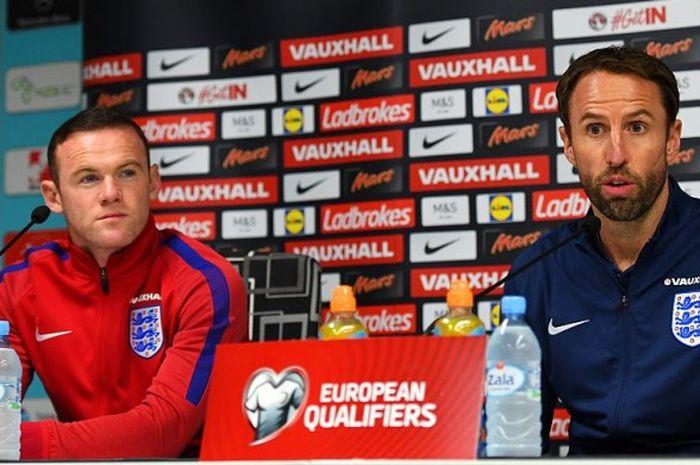 Wayne Rooney (kiri) dan manajer interim timnas Inggris, Gareth Southgate, saat melakoni jumpa pers menjelang duel Kualifikasi Piala Dunia 2018 lawan Slovenia di Ljubljana, 10 Oktober 2016.