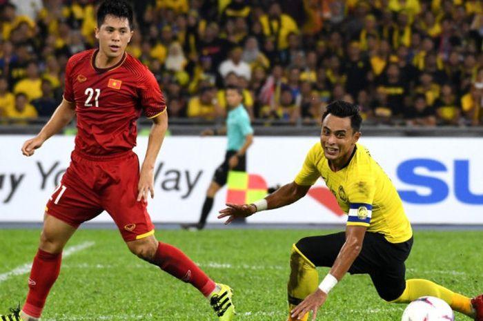Kapten timnas Malaysia, Zaquan Adha nyaris terjatuh seusai duel dengan bek timnas Vietnam, Tran Dinh Trong pada final pertama Piala AFF 2018 di Stadion Nasional Bukit Jalil, Kuala Lumpur, 11 Desember 2018.