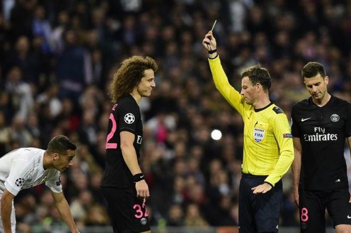 Wasit Mark Clattenburg (kuning) melayangkan kartu kuning kepada pemain belakang Paris Saint-Germain,